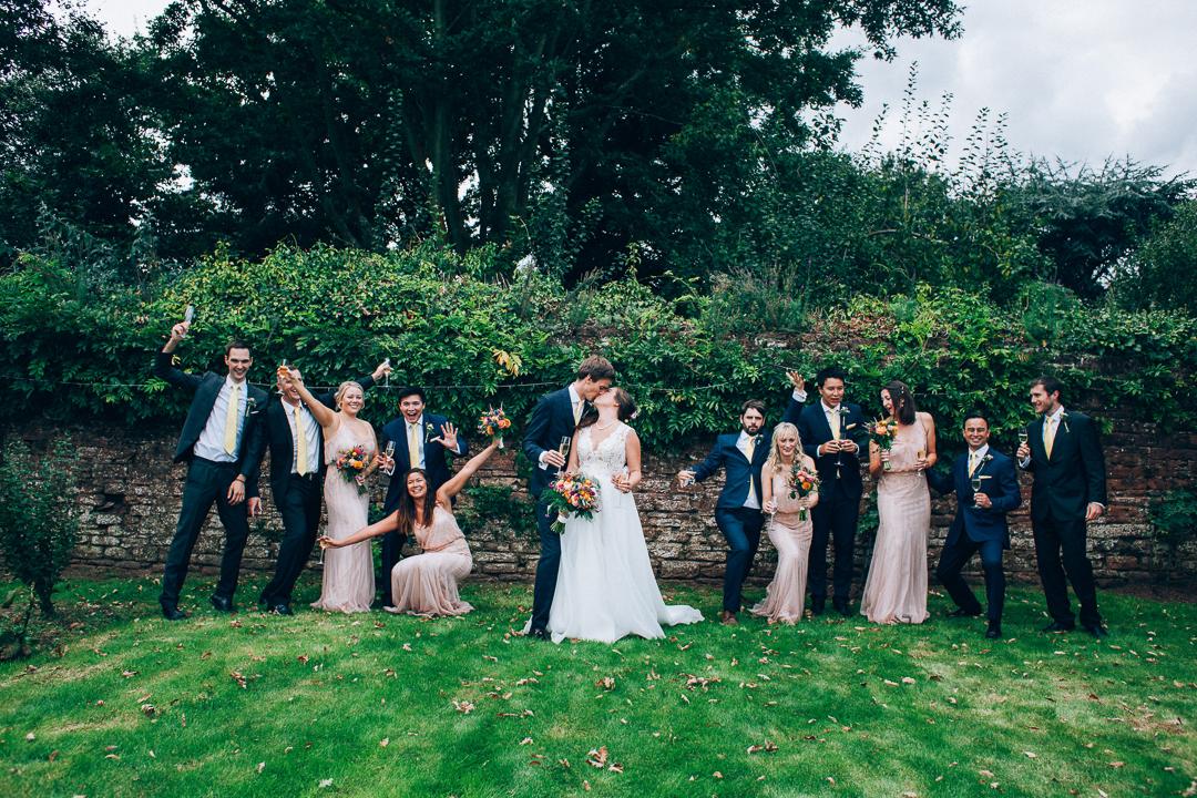 Devon colourful garden wedding bridesmaids & groomsmen fun group shot image