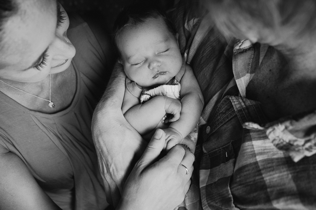 newborn baby cuddled by mum and dad image