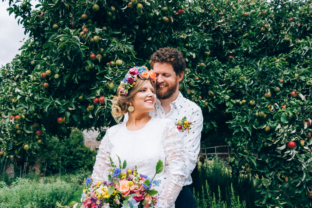 bride in flower crown with groom in front of apple tree image