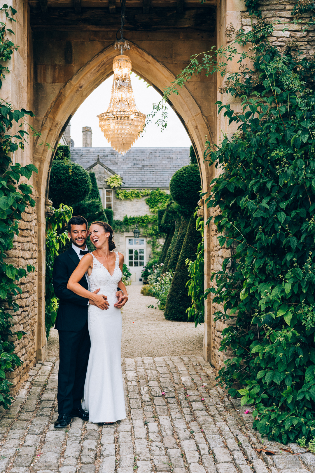 bride and groom laughing under the chandelier arch at the lost orangery image