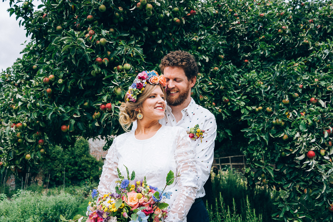 Bride & Groom portrait by the apple tree festival style flower crown laid back wedding image