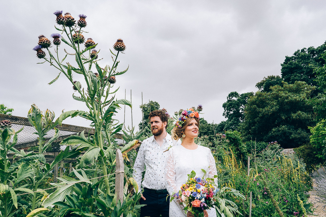 bride and groom portrait in the walled garden with giant purple thistle image