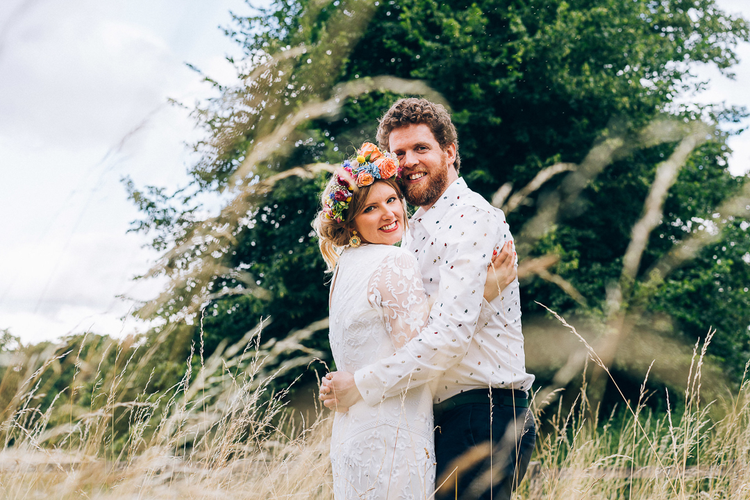 Bride and groom portrait in the long grass flower crown and smiles boho bride and laid back groom image