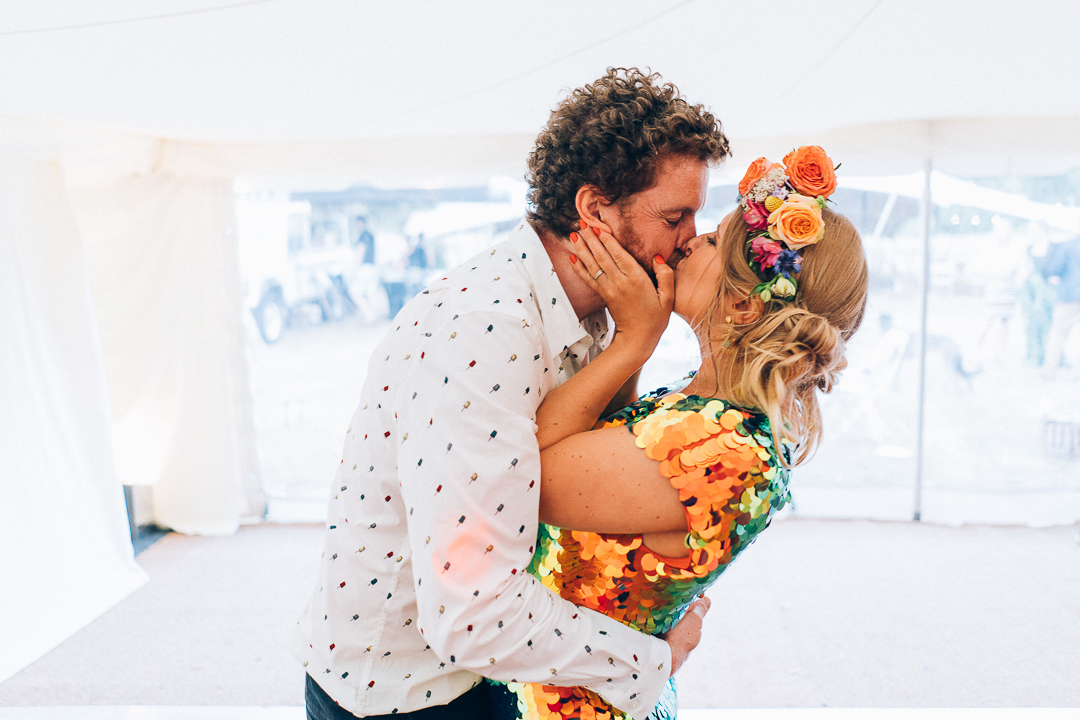 bride and groom kiss bride in rosa bloom sequin jumpsuit with flower crown image