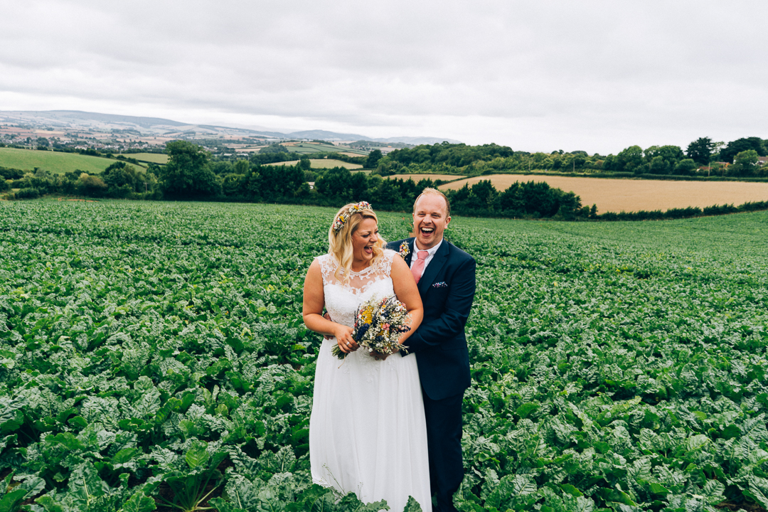 fun wedding photography somerset bride and groom in fields laughing image