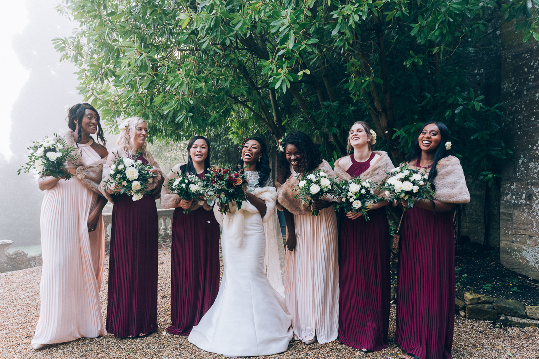 image of bride and her bridesmaids outside Brympton House laughing winter wedding