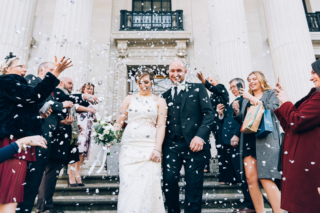 image of bride and groom and guests during confetti outside old Marylebone town hall