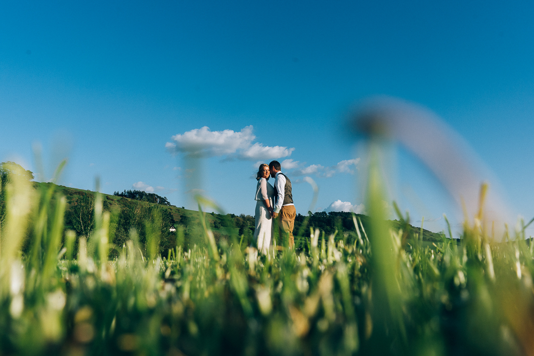image of bride and groom in somerset fields bright blue skies on their wedding day