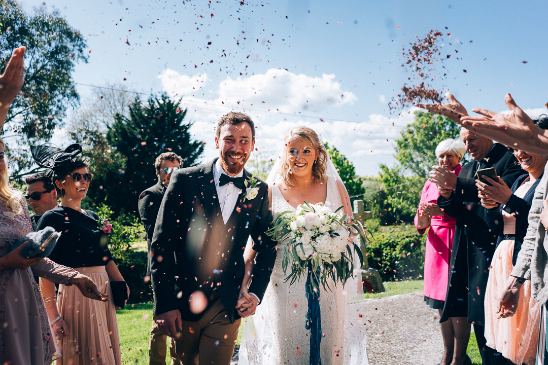 image of bride and groom outside church in south somerset smiling as confetti is thrown