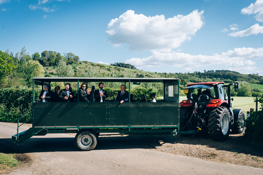 image of wedding guests arriving at the farm reception on a tractor trailor in the rolling somerset countryside