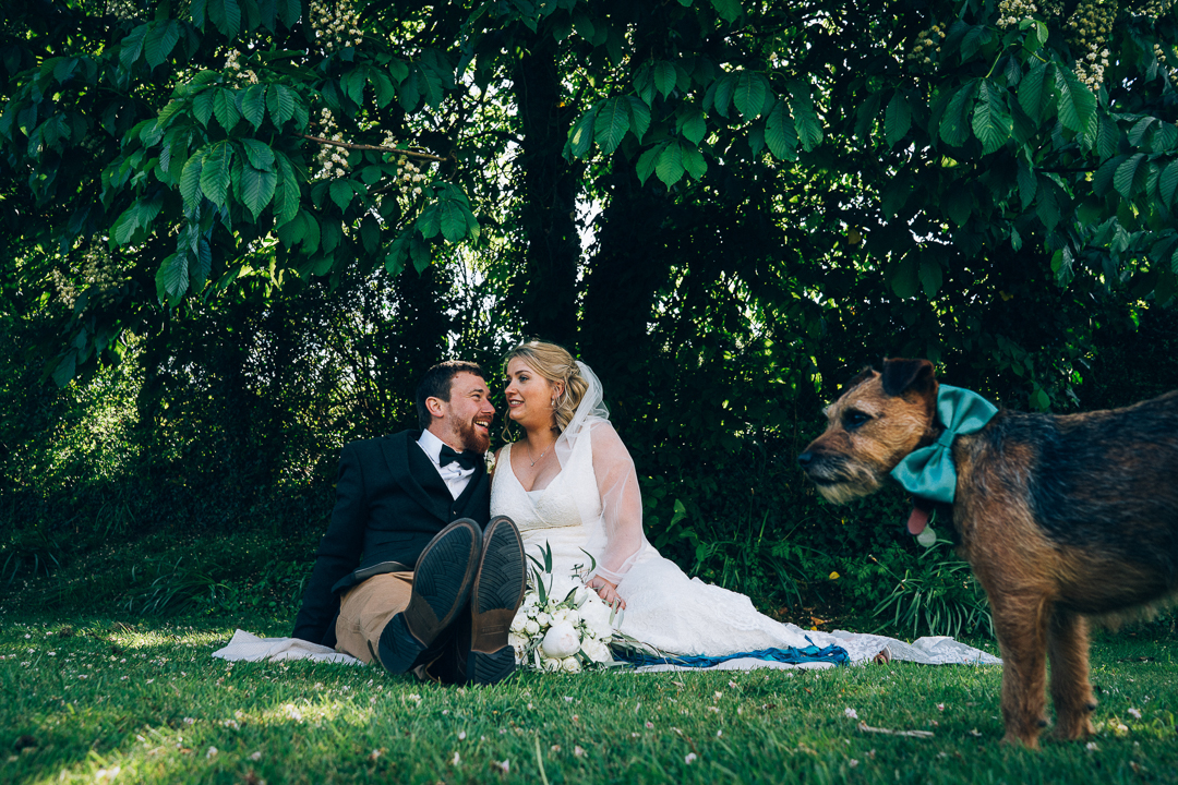 image of the bride and groom sat in the gardens on the farm for their wedding with one of their dogs