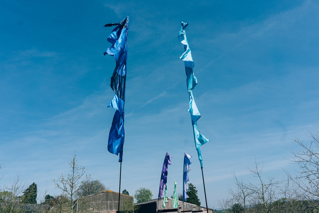 image of festival flags and blue sky for outdoor ceremony at the corn barn devon