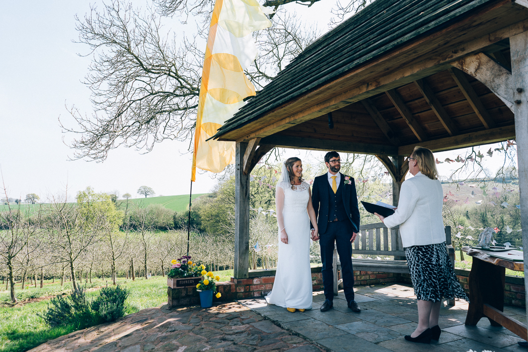 image of bride and groom during outdoor ceremony at the corn barn devon with festival flags