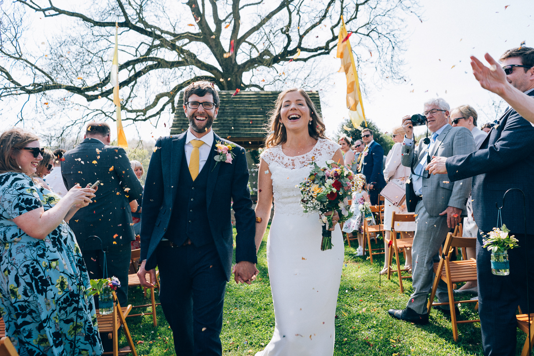 image of bride and groom walking back down aisle with confetti and festival flags at the corn barn cullompton
