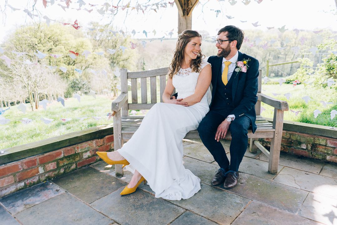 image of bride and groom on bench outside the corn barn cullompton