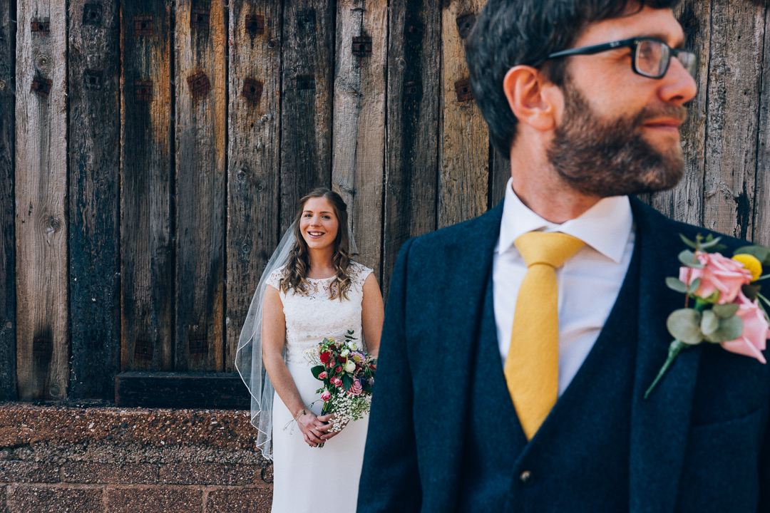image of bride and groom outside farm sheds at the corn barn cullompton bride with colourful flowers and groom wearing a yellow tie
