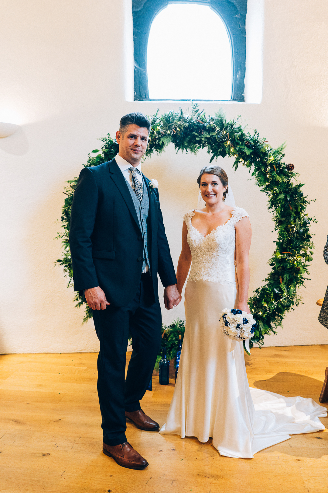image of bride and groom with foliage moon gate at the corn barn cullompton