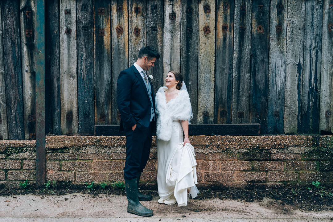 image of bride and groom portrait in their wellies at their corn barn cullompton winter wedding