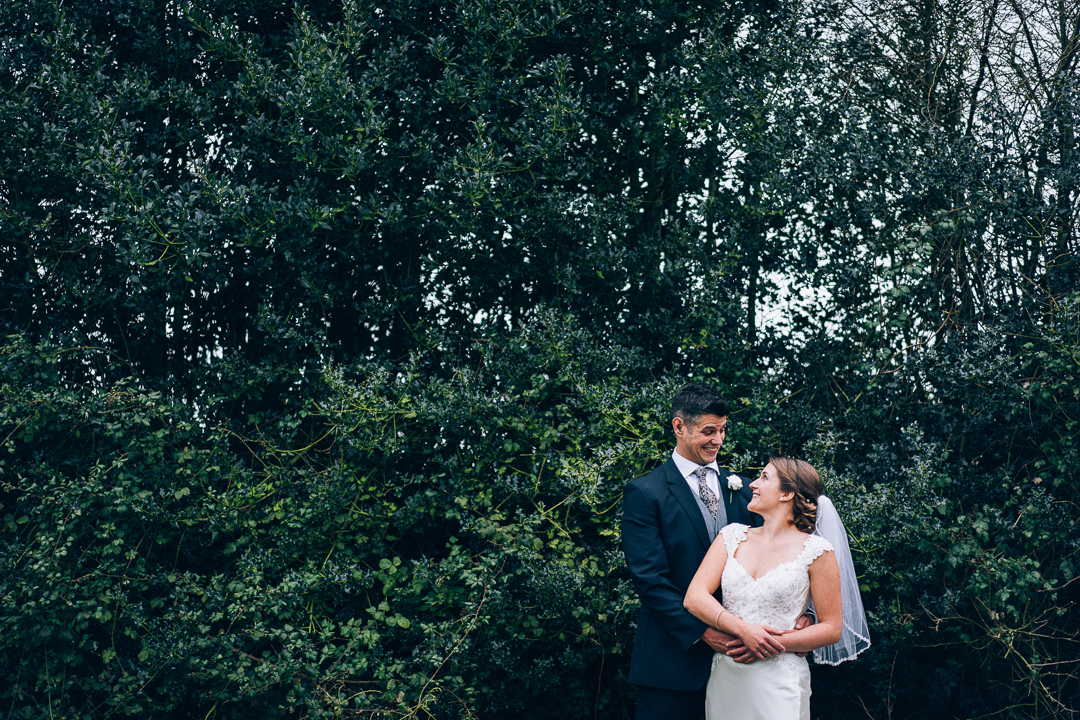 image of bride and groom by the trees at the corn barn cullompton