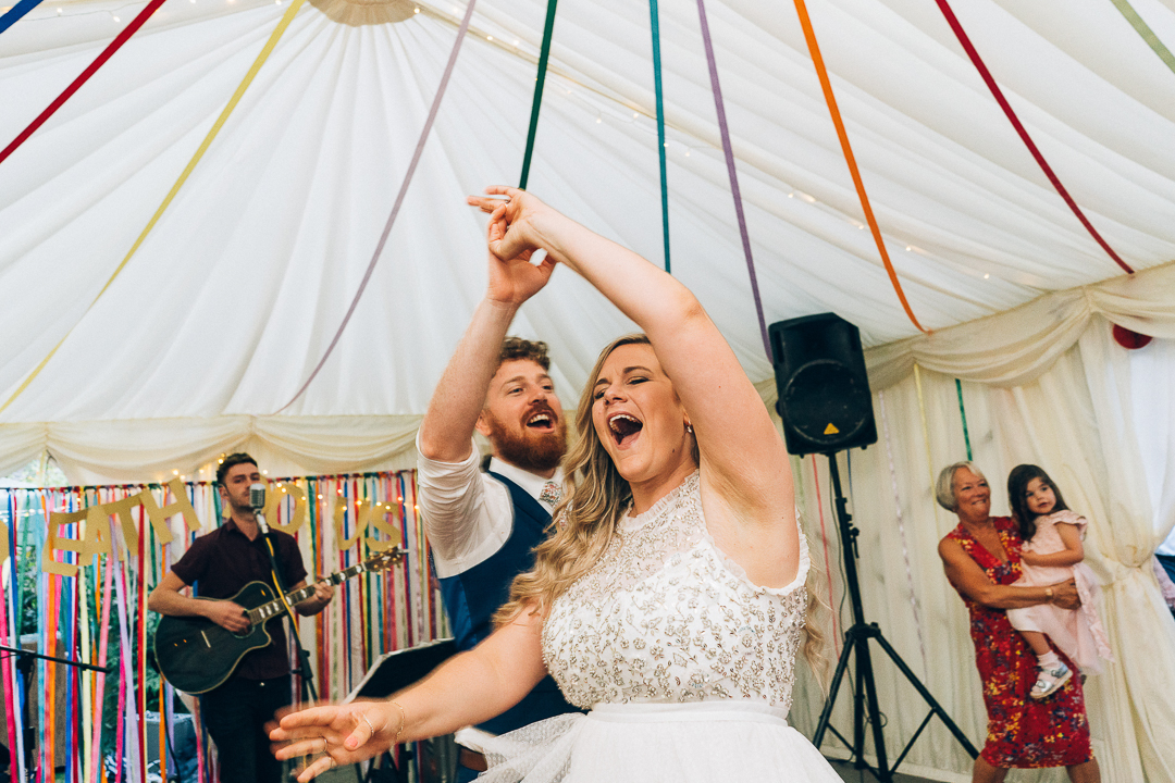 image of bride and groom first dance in marquee in the garden wedding with colourful streamers and band