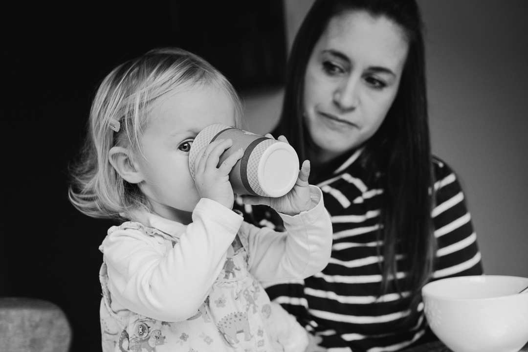 image of toddler peeping behind her drink cup with her mum during family photography session in devon