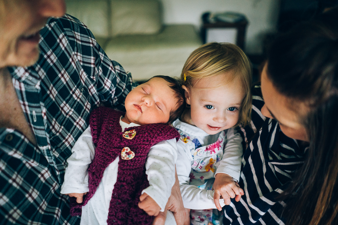 image of toddler and her new baby sister at home in devon during their family photography session