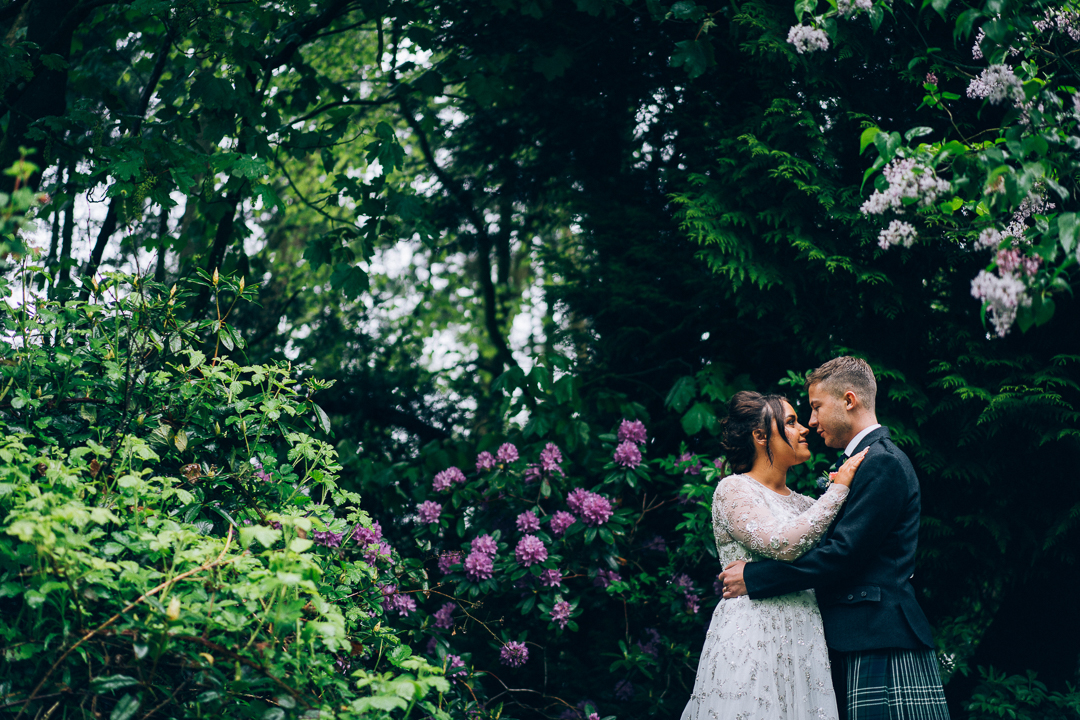 image of bride and groom in the trees with pink flowers at Tullibole castle